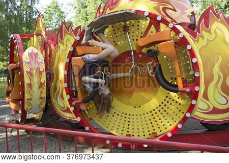 A Teenage Girl Is Riding Alone On A Swing, Amusement Carousel, The Child's Face Is Not Visible. One