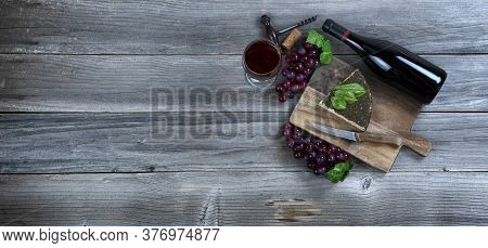 Red Wine With Fresh Cheese Wedge Plus Basil Leaves And Grapes On Rustic Wood With Copy Space Availab