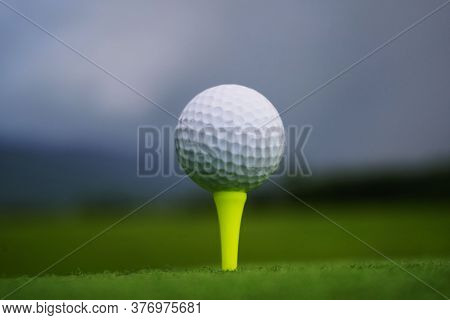 Golf Ball On Tee In Beautiful Golf Course At Sunset Background. Golf Ball On Green In Golf Course At