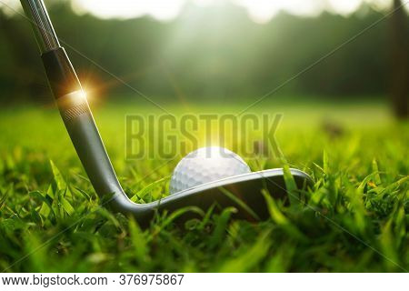 Blurred Golf Ball And Golf Club In Beautiful Golf Course At Sunset Background.