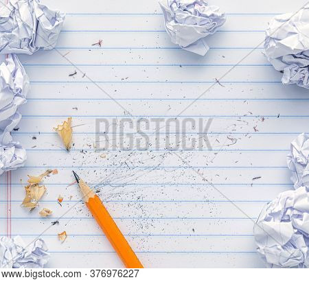 School supplies of blank lined notebook paper with eraser marks and erased pencil writing, surrounded by balled up paper and a sharp pencil. Studying or writing mistakes concept.