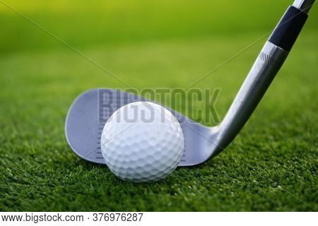 Golf Ball And Golf Club In Beautiful Golf Course At Sunset Background. Golf Ball On Green In Golf Co