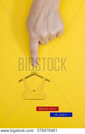 Bikini Top On A Clothes Hanger And A Female Hand. July 5th Bikini Day Date