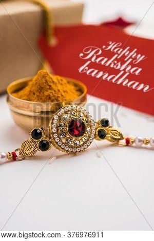 Indian Festival Raksha Bandhan With Rakhi Bracelets, Presents, Rice And Kumkum In Bowls. Copy Space