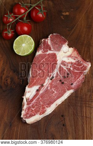 Fresh Raw T Bone Steak On Wooden Board  Background With Tomato, Pepper, Kiwi, And Rosemary In A Rust