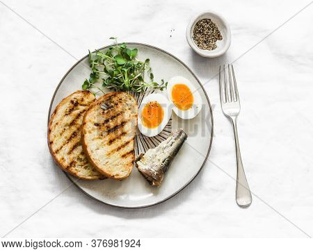 Grilled Bread, Canned Sardines, Boiled Eggs, Micro Greens On A Light Background, Top View. Delicious
