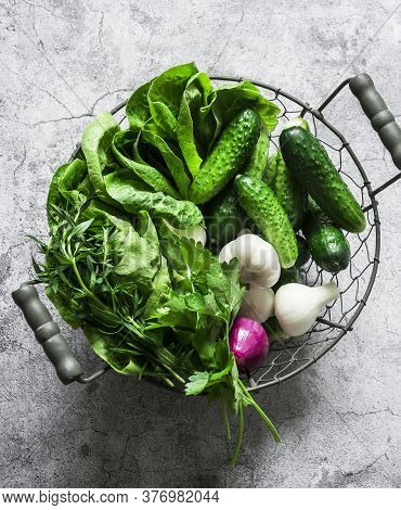 Fresh Vegetables Cucumbers, Romaine Lettuce, Onions, Herbs In A Metal Vintage Basket On A Gray Backg