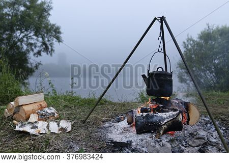 The Kettle Is Heated On The Fire In The Evening. Tourist Camping By The River. Travel To Siberia. Pi