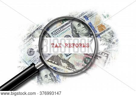 Tax Reforms, Inscription, On A Background Of Dollar Bills. View Through A Magnifying Glass. Isolated