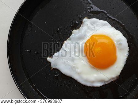 Fried Egg On A Black Skillet . Food Close Up.