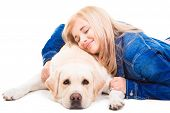 beautiful girl in blue embracing pale-yellow Labrador retriever dog on the isolated white background poster