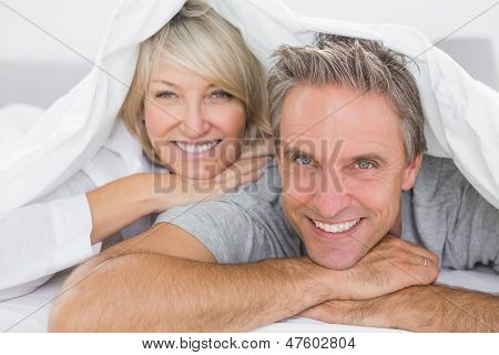 Couple smiling under the covers at home in bed