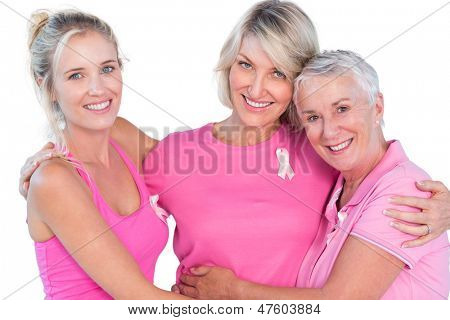 Women wearing pink tops and ribbons for breast cancer on white background