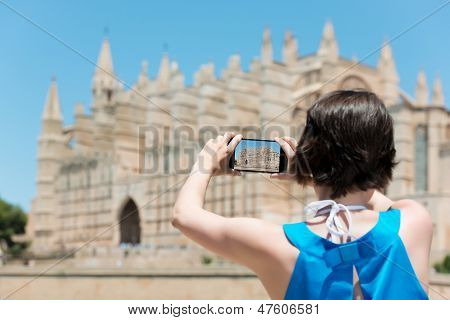 Woman tourist in Mallorca taking photographs of landmark buildings while enjoying the adventure of a a summer vacation in Europe view from behind poster