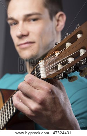 Close-up Of Young Man With Guitar  Over Gray Background