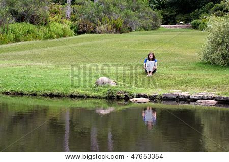 Woman Reading Newspaper Sitting In Grass