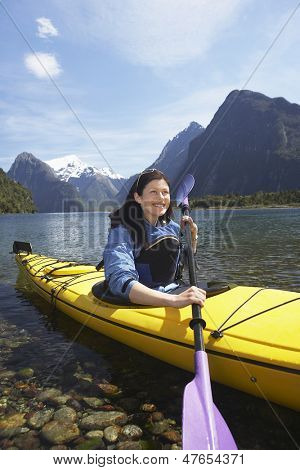 Young woman kayaking in lake with mountains in background
