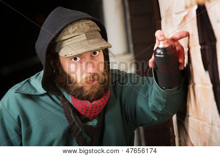 Serious man with hood spray painting a wall poster