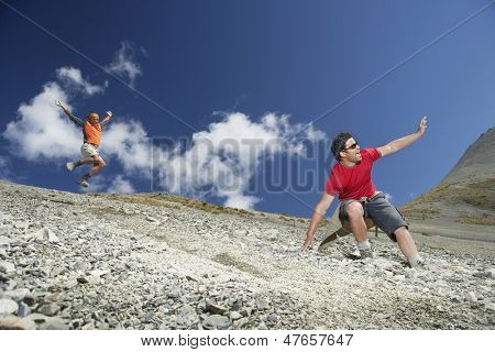 Low angle view of two men sliding down scree field