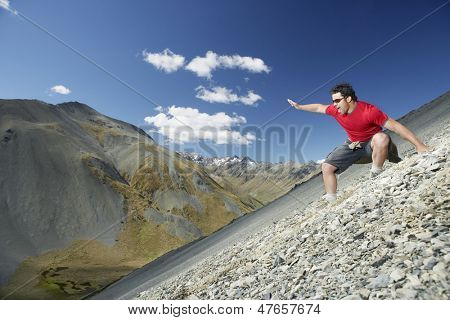Side view of a young man sliding down scree field