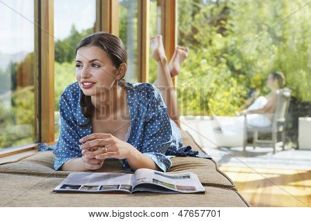 Woman with magazine near windows overlooking forest