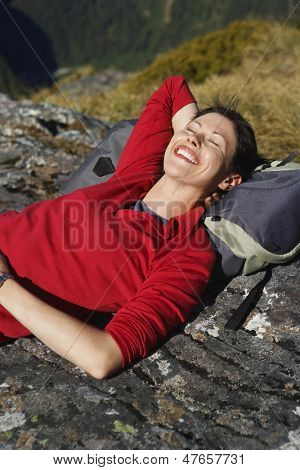 Smiling young woman lying on boulder with head over backpack