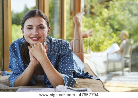 Portrait of a young woman with magazine by windows overlooking forest