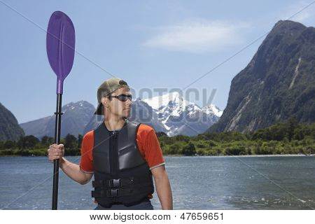 Young serious man holding an oar on shore of mountain lake