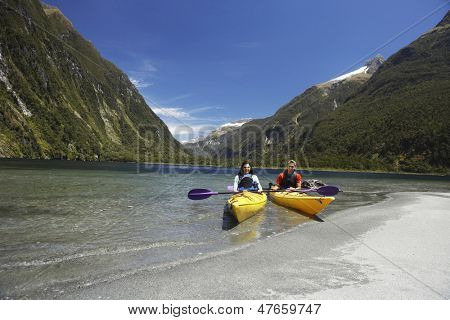 Two young people kayaking in the lake with mountains in background