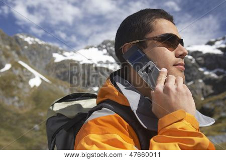 Side view of a young male hiker using cellphone against the mountains