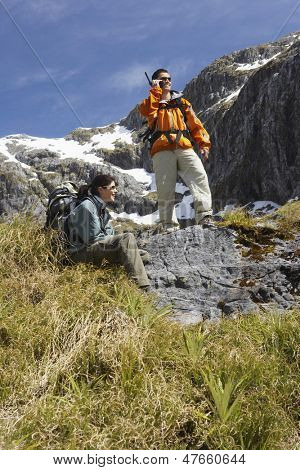 Man using walkie talkie while a woman rests on rock on hiking trail in mountains