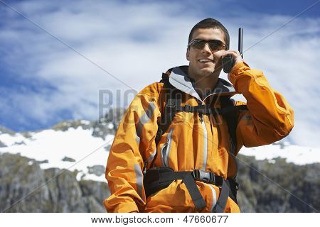 Smart smiling man using walkie talkie against blurred snow capped mountain