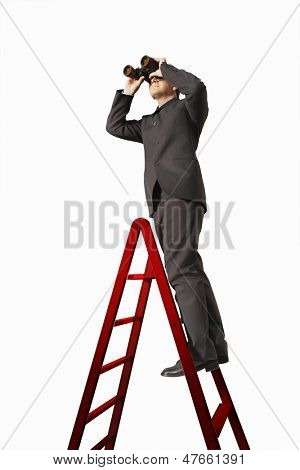Full length of businessman on ladder looking through binoculars isolated on white background