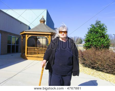 Senior Woman Walking With Cane Outside