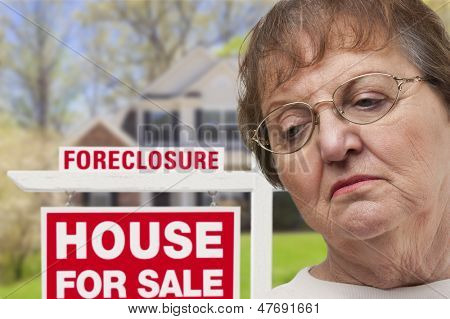 Depressed Senior Woman in Front of Foreclosure Real Estate Sign and House.