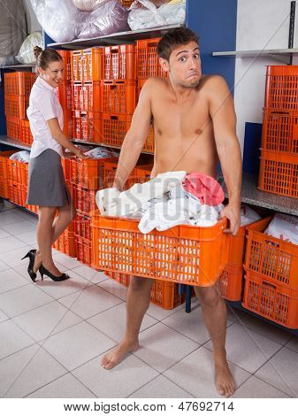 Portrait of semi nude young man holding clothes basket with businesswoman looking at him in laundromat