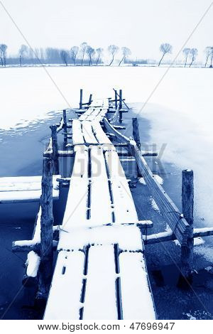 Simple Bridge In The Pond In The Snow In Rural