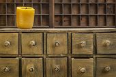 bee wax candle in retro setting with a primitive apothecary drawer cabinet poster