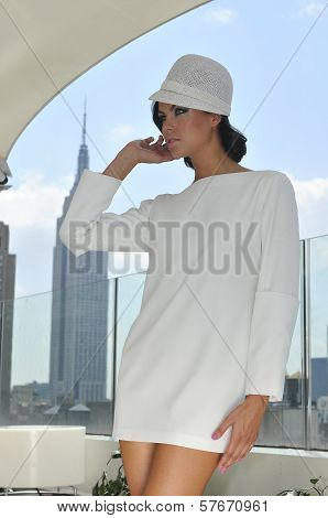 Model wearing couture white dress and posing on the rooftop
