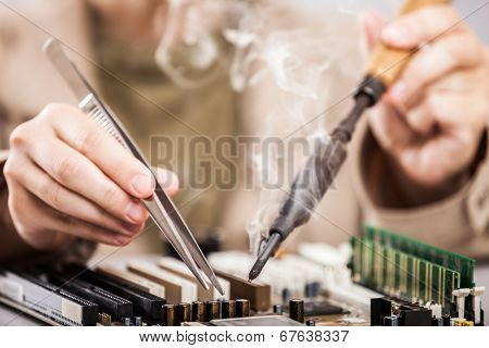 Manual worker human hand holding soldering iron tool repairing computer electronics circuit board