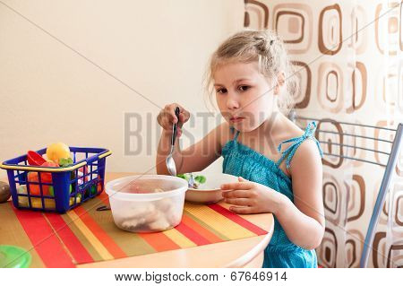 Girl In Blue Dress Eating Porridge At Table And Plays With Her Toys