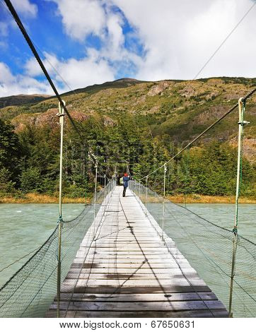 Suspension bridge across mountain river. In the middle of the bridge woman - tourist photographs the raging torrent
