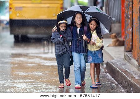 BANAUE, PHILIPPINES, DECEMBER 03 : Little girls are walking under the rain sheltering with an umbrella in the street of Banaue village, north Luzon, Philippines, on december 03, 2013