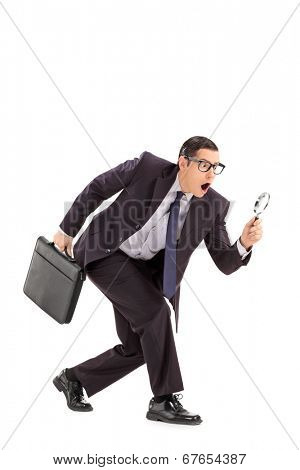 Sneaky businessman looking through a magnifying glass isolated on white background