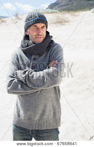 Attractive man shivering on the beach in hat and scarf on a bright but cool day