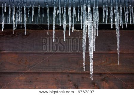 Icicles Hanging From A Drainpipe On A Wooden Panelled House