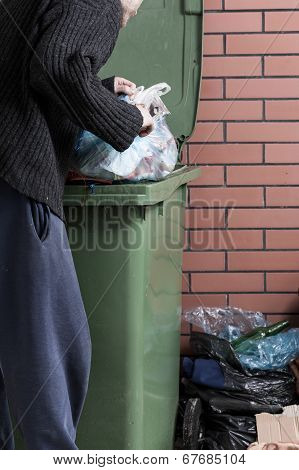 Hungry Homeless Man Looking For Food In A Dumpster