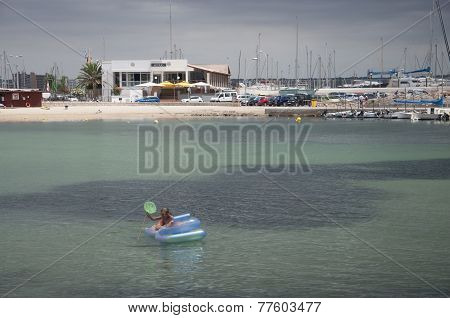 Girl Fishing From An Inflatable Beach Toy