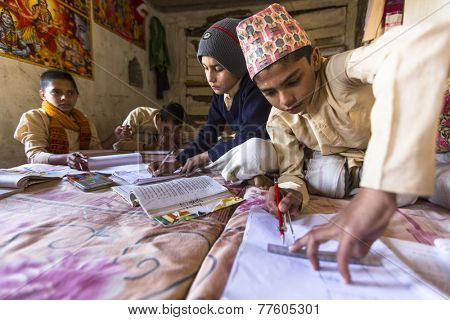 KATHMANDU, NEPAL - DEC 9, 2013: Unknown children doing homework at Jagadguru School. School established at 2013, to let new generation learn Sanskrit and preserve Hindu culture.