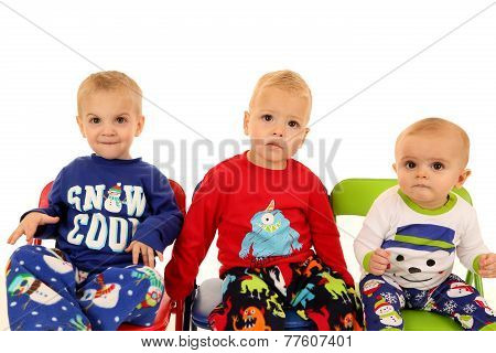 Three Cute Young Boys Sitting Wearing Winter Pajamas
